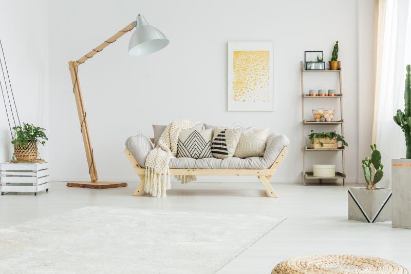 Beige sängöverkast som ligger på den gråa soffan fotografering för bildbyråer