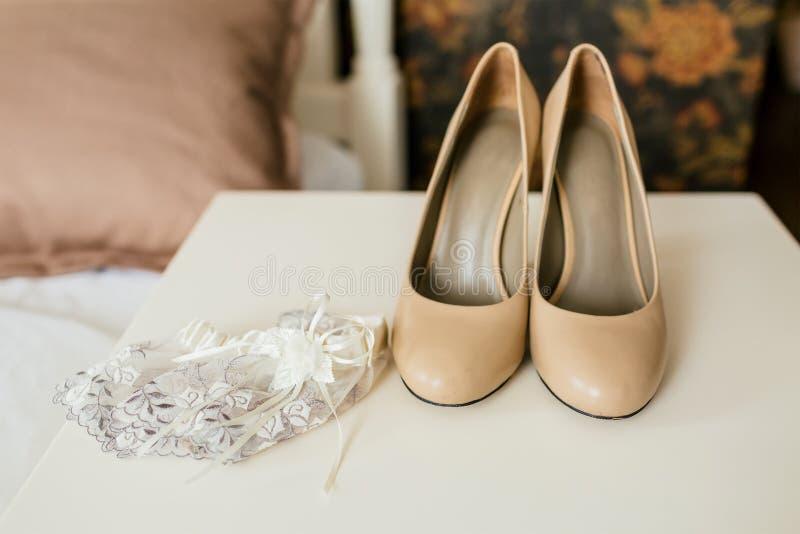 Beige schoenen op hielen en kantkouseband op een witte lijst Kousebanden en kousen kunstwerk royalty-vrije stock afbeeldingen