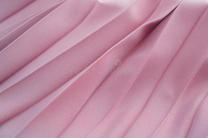 Beige silk or satin fabric folded background. Luxurious fabric cloth fold glamour background. Tender and elegant pink silk royalty free stock images