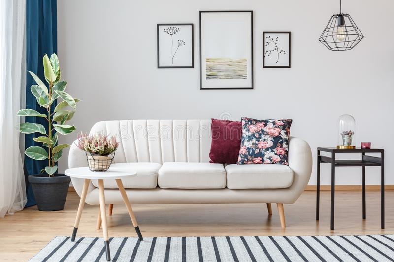 Beige sofa with wooden legs. Elegant, beige sofa with wooden legs and decorative pillows in bright living room interior royalty free stock images