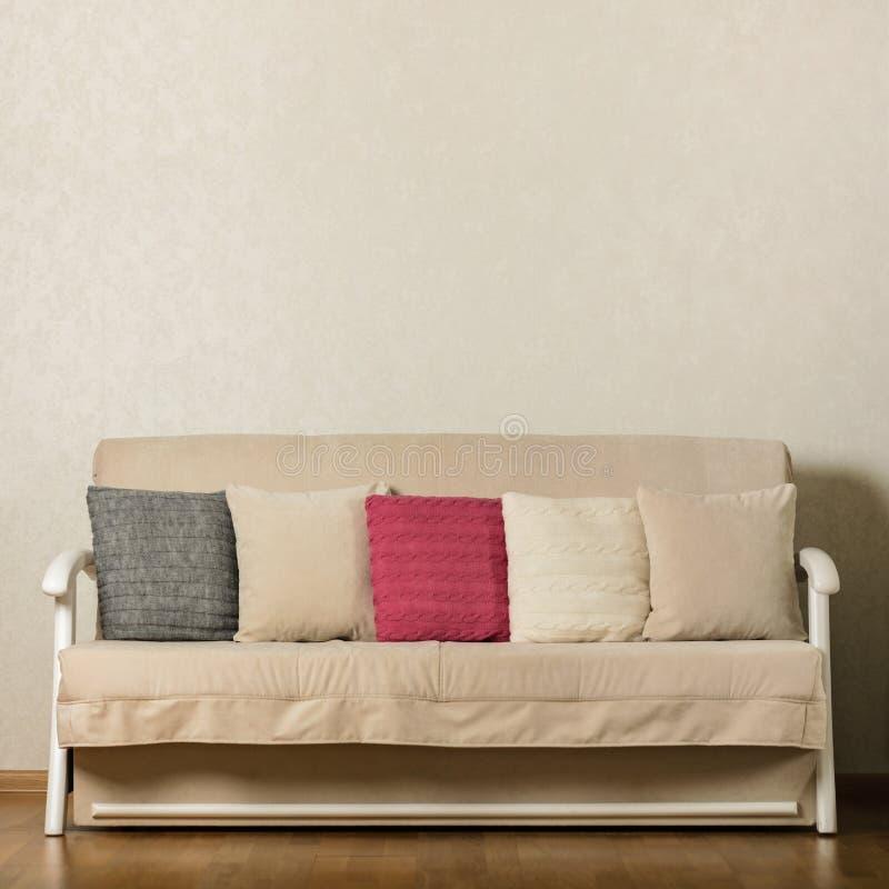 Beige soffa med färgrika kudderosa färger, grå färger, vit i vardagsrummet royaltyfri bild