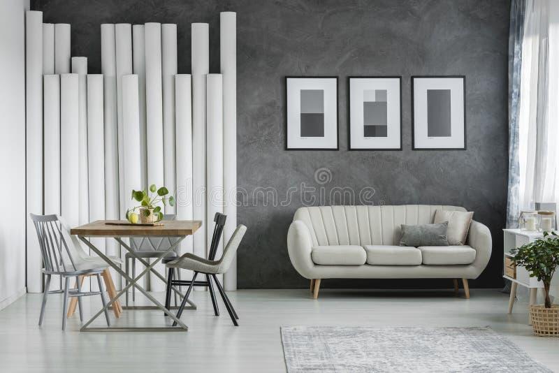 Beige soffa mot betongväggen fotografering för bildbyråer