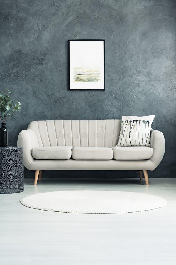Beige soffa mot betongväggen royaltyfria bilder