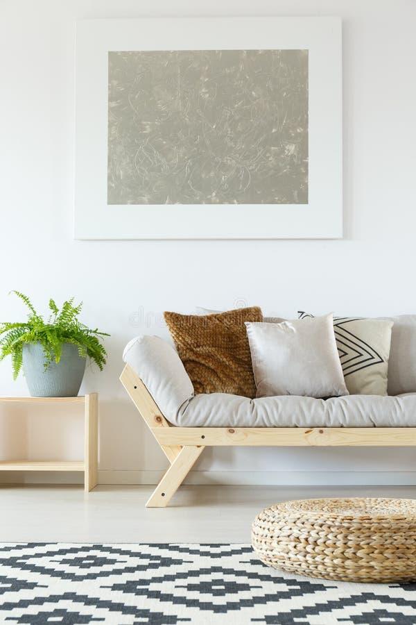 Beige soffa, puff och växter royaltyfria bilder