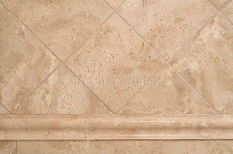 Beige Stone Tiles on Bathroom Wall. Horizontal of beige travertine stone tiles in a diamond pattern on a bathroom wall with matching edging strip running stock photography