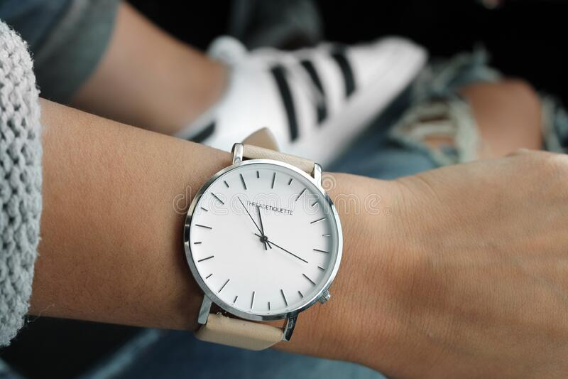 Beige Strap Silver Round Analog Watch Behind Adidas White and Black Superstar stock image