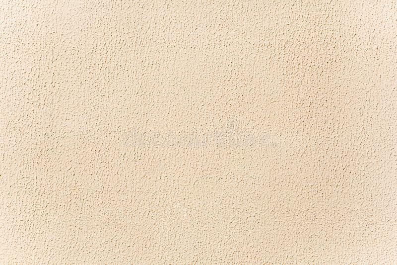 Beige stucco background. Bright wall lit by sunshine royalty free stock photography