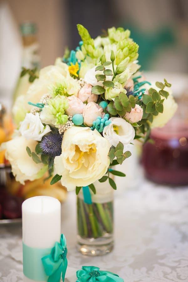 Beige Türkisblumen des Hochzeitsblumenstraußes in einem transparenten Vase stockbild
