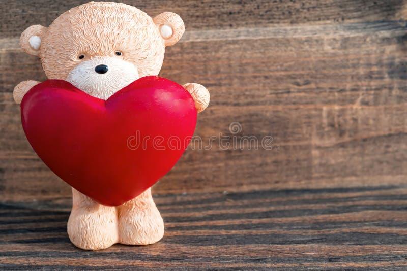 Beige Teddybär des hölzernen Spielzeugs mit großem rotem Herzen auf Weinleseholzoberflächehintergrund, Draufsicht, Kopienraum, fl stockfotografie