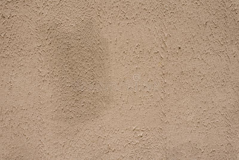 Beige textured wall, background. Structural plaster coated with water-based acrylic paint. Rough, uneven surface beige. Copy space royalty free stock images