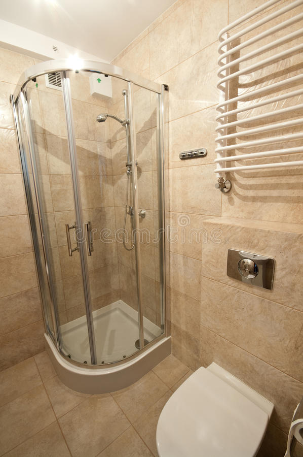 Beige bathroom. Beige tiles bathroom with shower cabin and toilet royalty free stock images