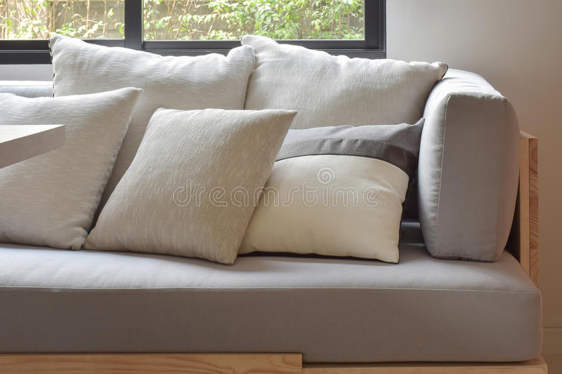 Beige varies size pillows setting on light gray comfy sofa royalty free stock images
