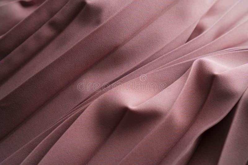 Beige vikt bakgrund för silke eller för satäng tyg Lyxig bakgrund för glamour för tygtorkdukeveck Mjukt och elegant rosa silke arkivbild