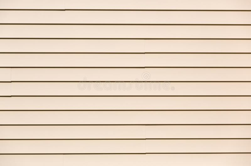 Beige vinyl siding. Wide view of rows of beige vinyl siding in bright sunshine stock image