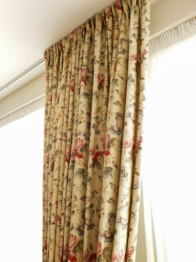 Beige Vorhänge der Weinlese, die am Fenster mit buntem Muster in einem hellen Raum hängen stockfoto