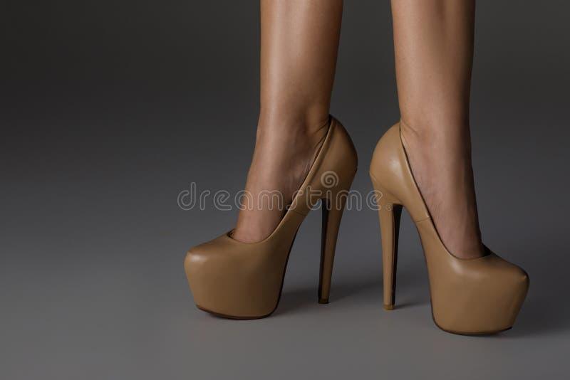Beige vrouwen` s schoenen Vrouw in hoge hielenschoenen stock afbeelding