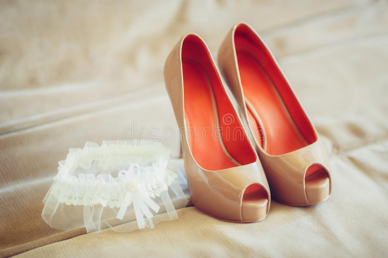 Beige bridal shoes with garter on sofa, marriage concept. Beige wedding bridal shoes with garter on sofa, marriage concept royalty free stock image