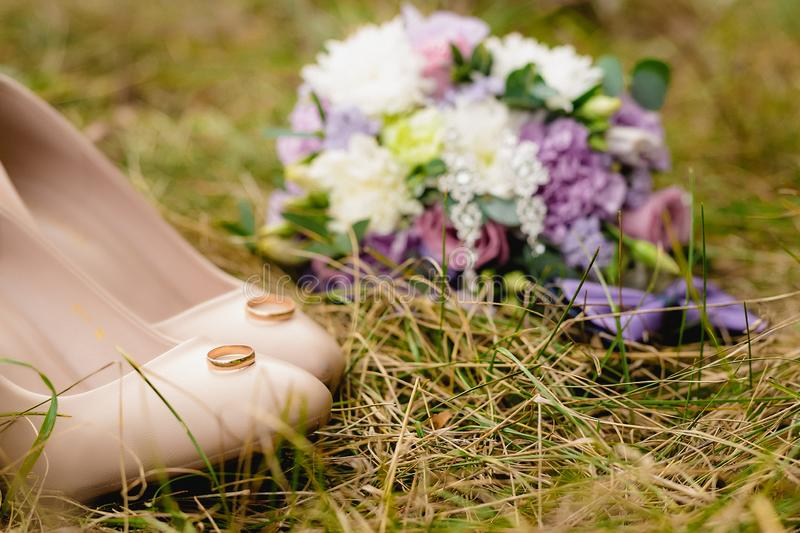 Beige wedding shoes, pair of engagement rings, bow-tie and bouquet on the grass. stock photo