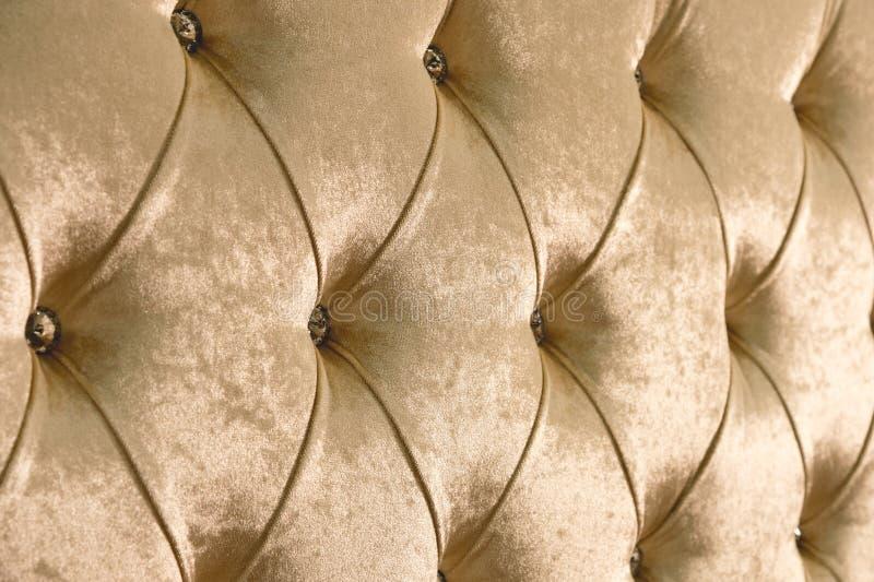 Beige weicher Textilhintergrund mit symmetrischen Knöpfen auf den Ecken von Diamanten Weiche und teure Möbelelemente lizenzfreies stockfoto
