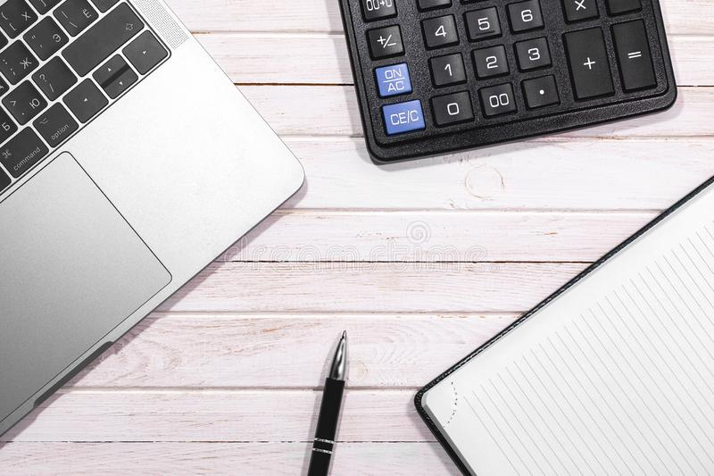 Beige wooden desk table with pen, notepad, calculator and Macbook. Apple Inc. is an American multinational technology company. royalty free stock image