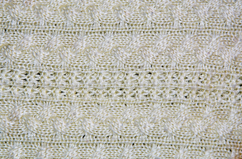 Beige wool knitted fabric with patterns closeup. The beige wool knitted fabric with patterns closeup royalty free stock image