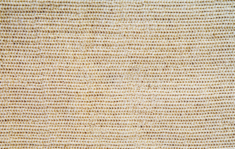 Beige wool knitted fabric with patterns closeup. The beige wool knitted fabric with patterns closeup stock images