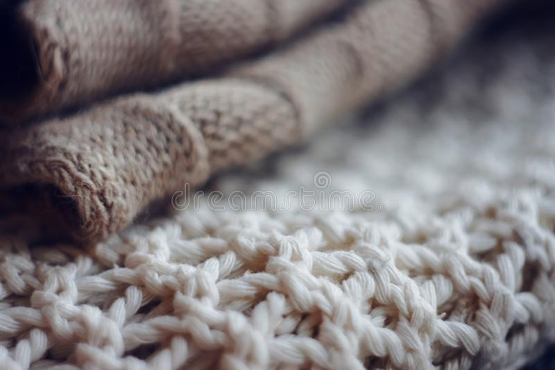 Beige wool sweater and white jumper large knit. Lie in a pile on top of each other royalty free stock image
