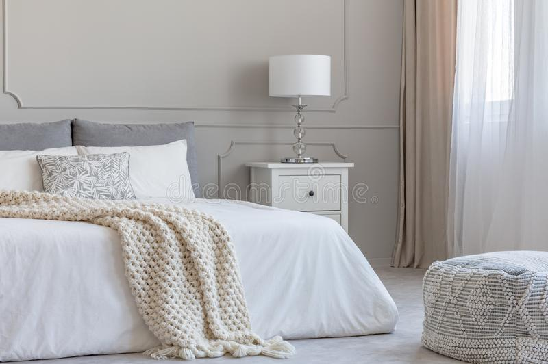 Beige woolen Decke auf weißer Daunendecke auf Königgrößenbett im eleganten Schlafzimmerinnenraum lizenzfreies stockfoto