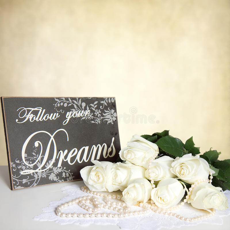 BeigeTexture-Hintergrund - weiße Rosen - Perlen - hölzernes Zeichen lizenzfreie stockfotos