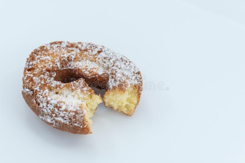 Beignet avec du sucre en poudre et un manquer de morsure d'isolement sur le fond blanc - image images stock