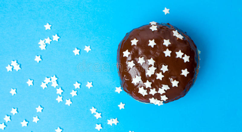 Beignet décoré de chocolat sur le fond bleu photos libres de droits