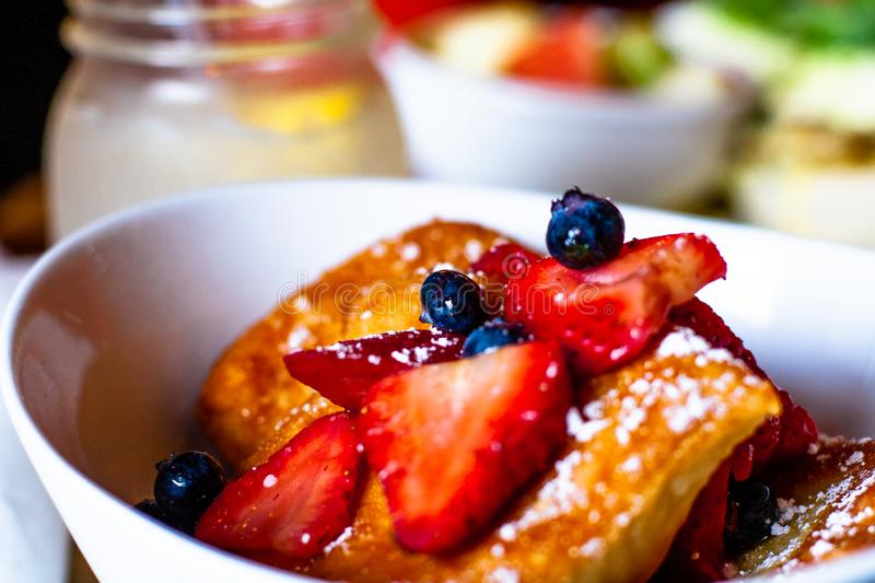 Beignet with fruit and blueberries for breakfast. A bowl full of beignet topped with bright red strawberries and blueberries covered with syrup stock photo
