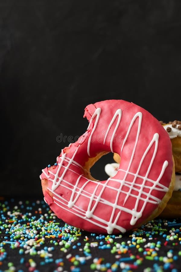 Beignet givré rose avec manquer de morsure photos stock