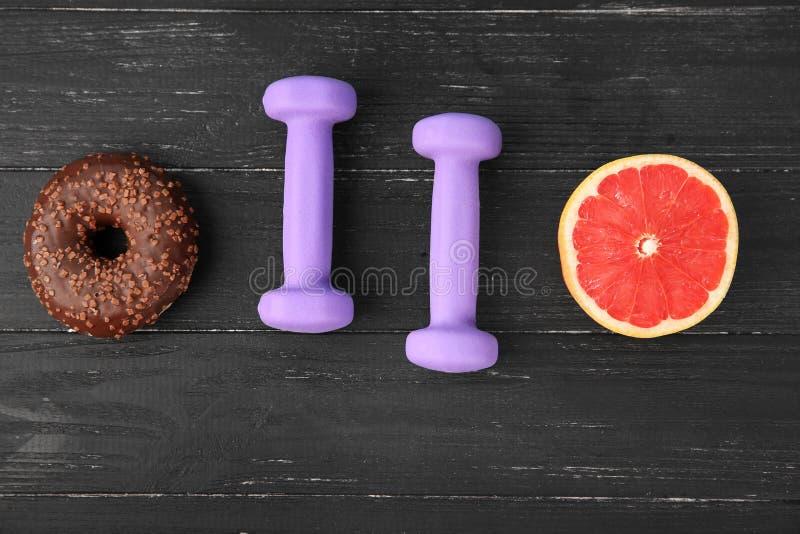 Beignet, pamplemousses et haltères de chocolat sur le fond en bois Choix entre le r?gime et la nourriture malsaine photos libres de droits