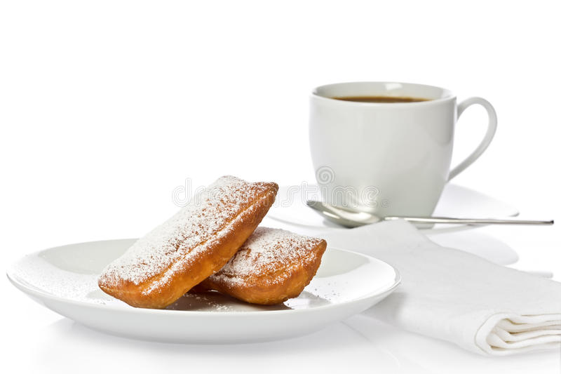 Beignets. Two New Orleans style beignets with a cup of coffee against a white background royalty free stock photography
