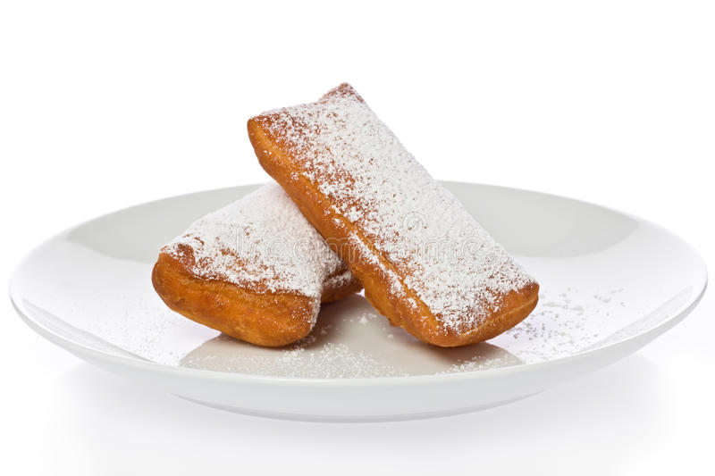 Beignets. Two New Orleans style beignets on a white plate against a white background stock photos
