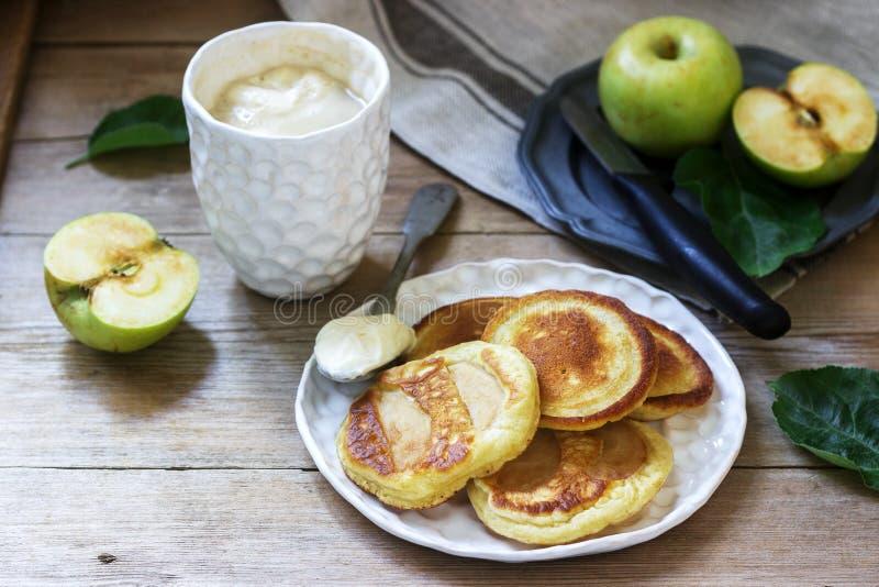 Beignets de pomme faits maison avec la crème sure, le café et les pommes vertes sur un fond en bois Type rustique photos libres de droits