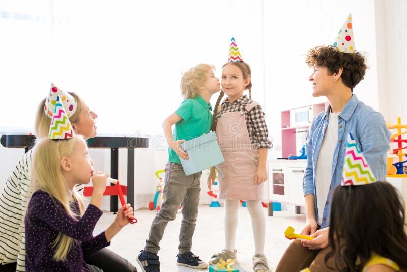 Beijando a menina para o presente na festa de anos das crianças imagens de stock royalty free