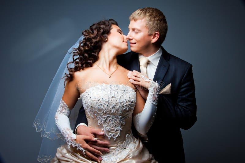 Beijando a noiva e o noivo fotografia de stock