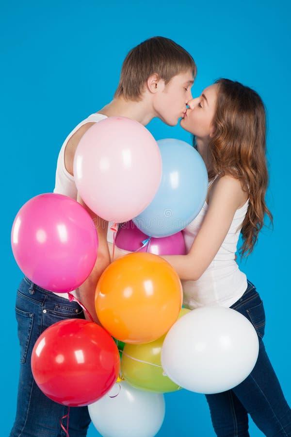 Beijando o amor novo acople guardarar muitos balões no estúdio fotografia de stock royalty free