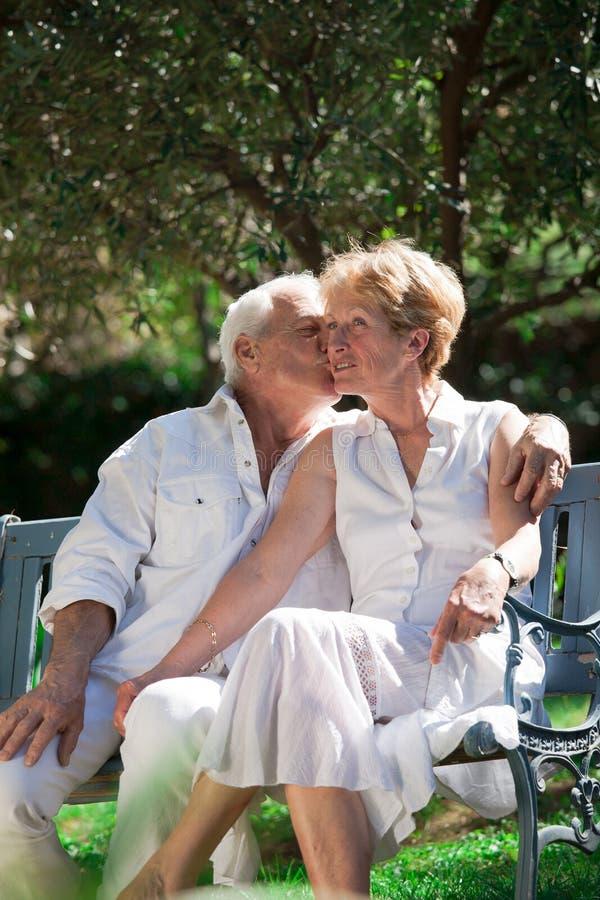Beijando pares idosos em um jardim fotografia de stock royalty free