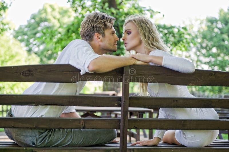 Beijando pares no banco foto de stock royalty free