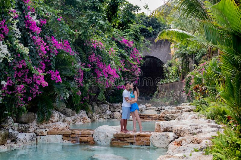 Beijar casal apaixonado Casal multiracial abraçando Casal multiétnico na piscina Piscina rodeada de rosa imagem de stock royalty free