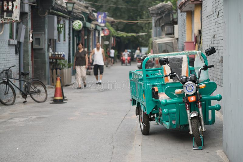Beijing, China - 08 04 2016: An adult tricycle, bike with three wheels in a hutong, in a street of Beijing, China.  stock photos