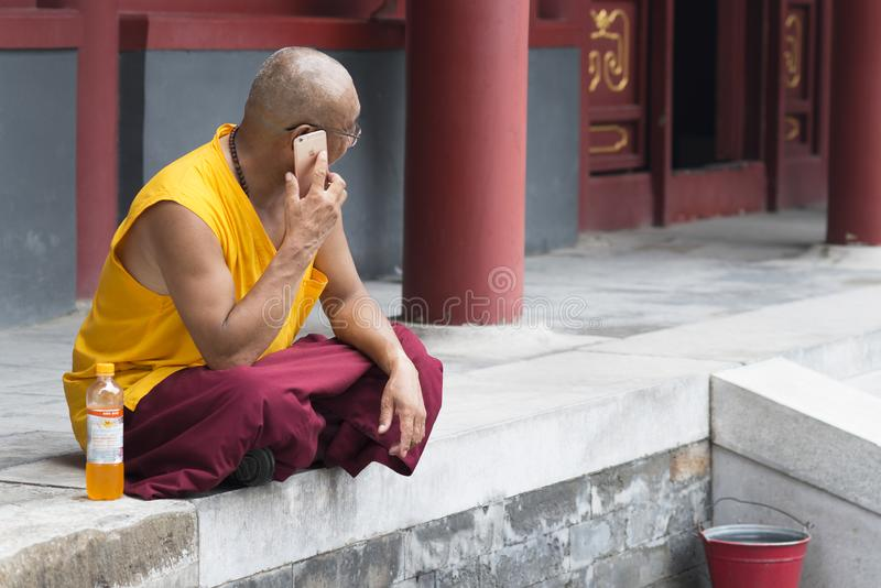 Beijing, China - 08 01 2016: An asian buddhist monk  talking on phone in front of a temple in Beijing, China royalty free stock images