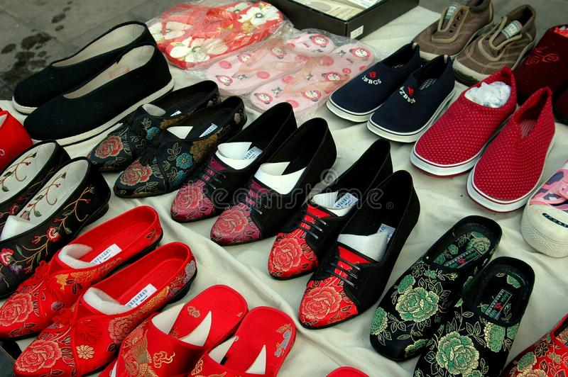 Beijing, China: Display of Chinese Shoes. A variety of traditional Chinese shoes, many decorated in brocade patterns, are displayed in front of a store in the royalty free stock image