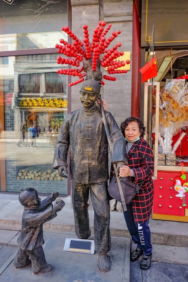 Portrait photo of Senior asian women with Selling Tang lu hu Chinese Famous local Food man statue in qianmen Street.Qianmen street stock photo