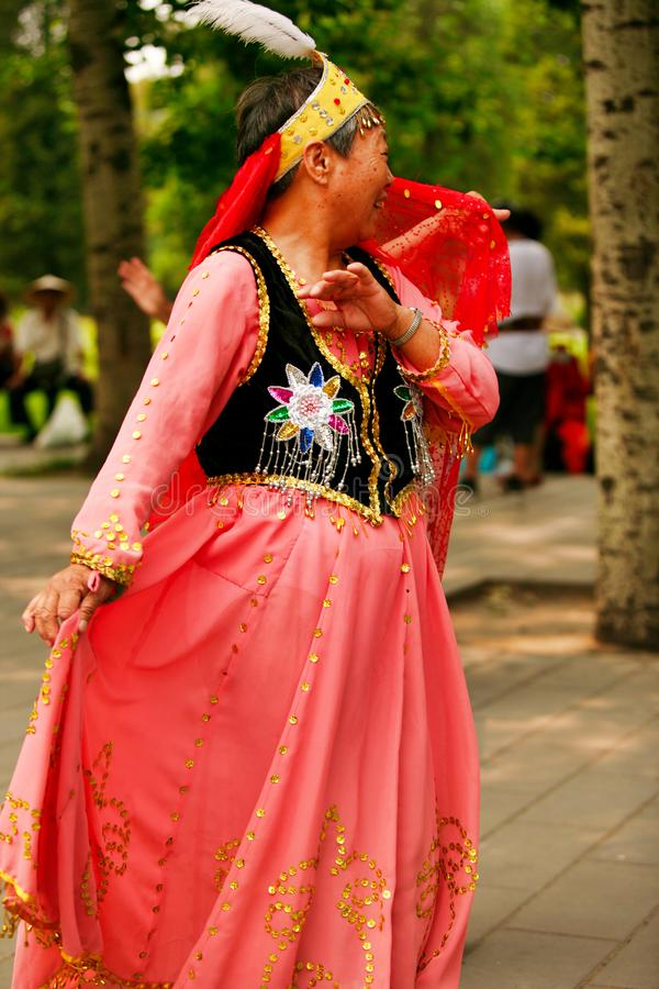 Beijing, China 07.06.2018 Happy Woman in red dress dance in the park royalty free stock photography
