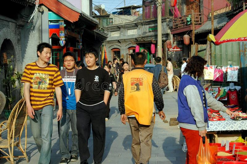 Beijing, China: Hutong Street Scene. Street scene in the crowded Shi Sa Hai Hutong with tourists, locals, and vendors sharing its narrow lanes and alleys in the royalty free stock photos