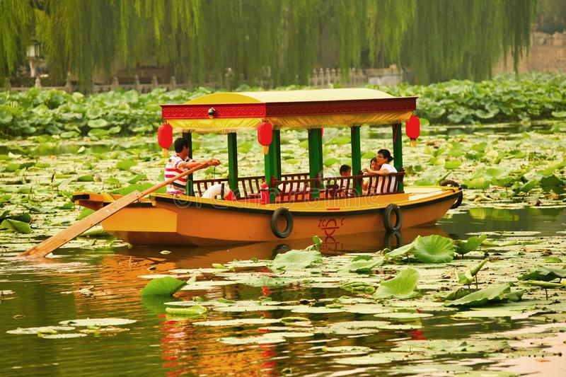 Beijing, China - June 9, 2018: Chinese tourists sail by boat on the Lake of Blessing in the Old Summer Palace. stock photography